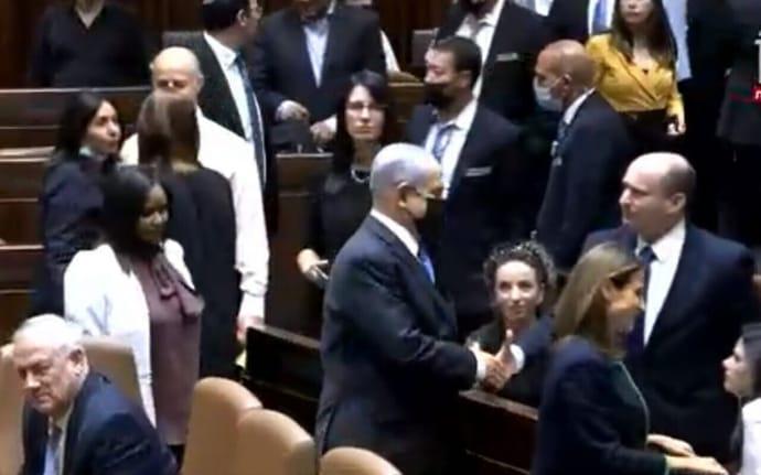 Нетаньяху обменивается рукопожатием в Кнессете с новоизбранным премьер-министром Нафтали Беннеттом