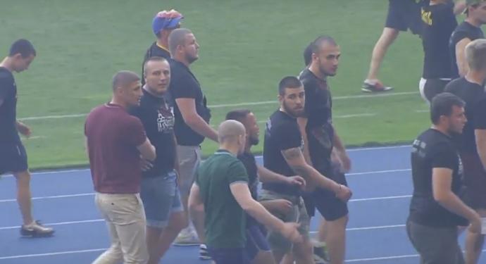 Олег Ширяєв (у зеленій футболці), відвернувшись від камери, щось розповідає Сергію Величку, у компанії харківських фанатів