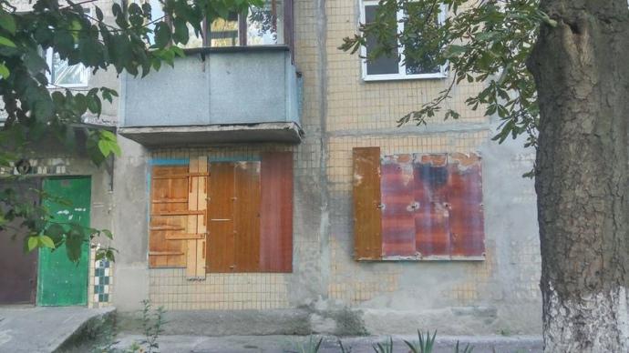 ФОТО 6— закладені вікна в хрущовці. Підпис: Закладені дошками вікна тих, хто після боїв січня-лютого 2015-го так і не повернувся у місто
