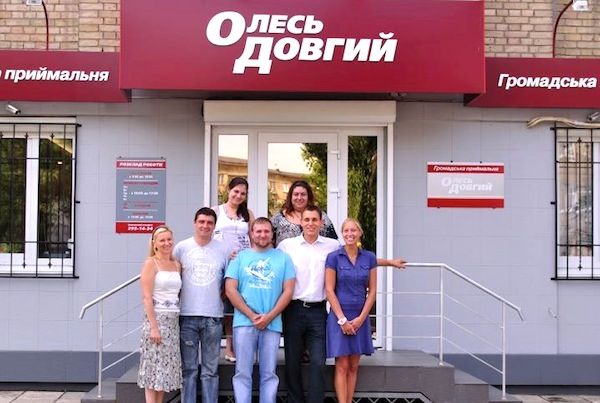 Олексій Новіков (нижній ряд, другий праворуч) та Марина Саакян (верхній ряд, праворуч) святкують відкриття приймальні Олеся Довгого