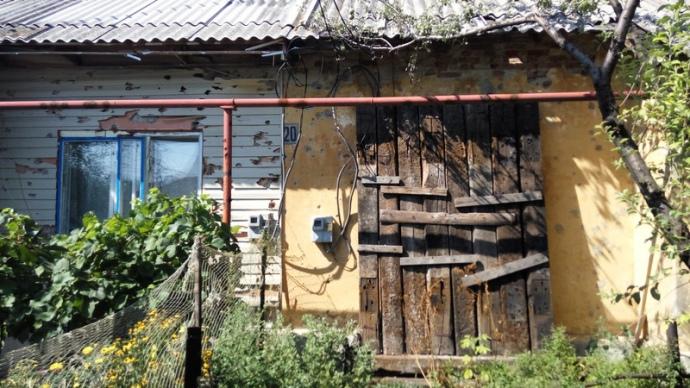 Вікно кімнати, в який лежить інвалід Олександр. Родичі заклали вікно шпалами, оскільки він не в змозі ховатися в підвалі
