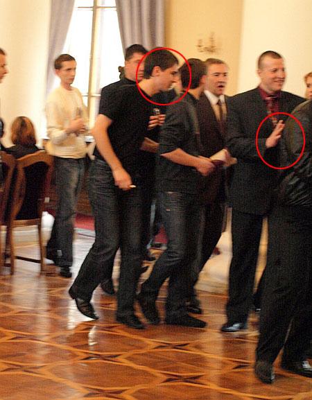 Охоронець (справа) і співробітник прес-служби мера (зліва) тримають Шкуріна. Журналіст стверджує, що йому допомогли йому не впасти